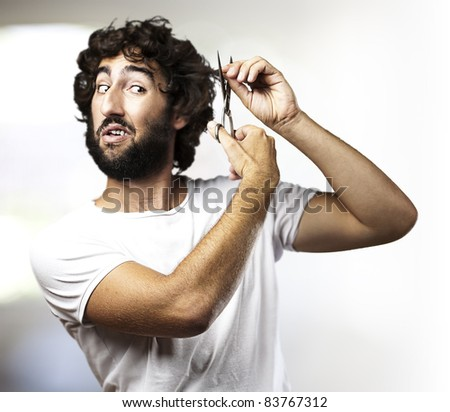 portrait of young man cutting the hair in a living room - stock photo