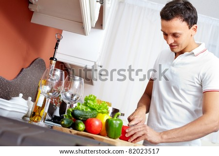 Portrait of young man cutting vegetables in the kitchen - stock photo