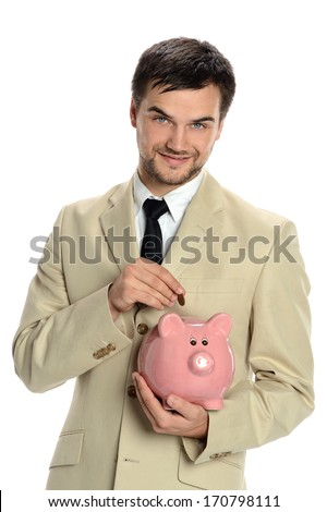 Portrait of young man depositing coin in piggy bank
