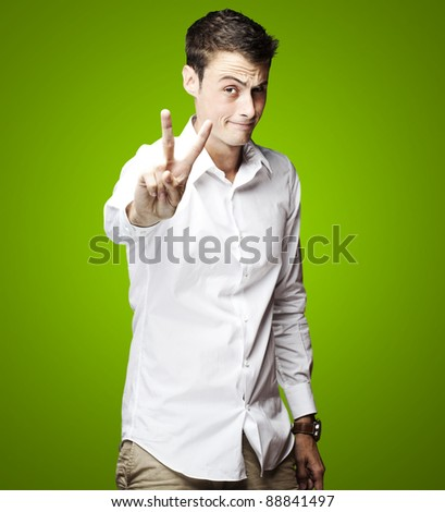 portrait of young man doing good symbol over green background
