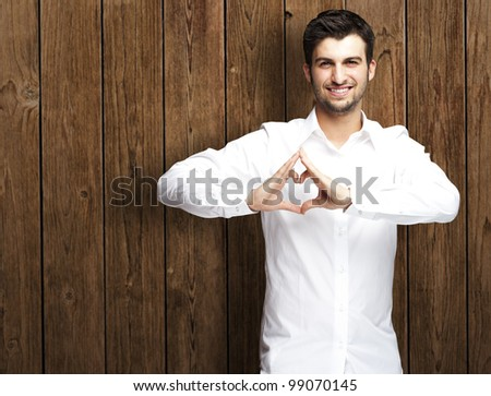portrait of young man doing heart gesture against a wooden wall