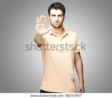portrait of young man doing stop symbol over grey background