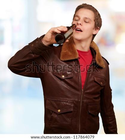 portrait of young man drinking beer indoor - stock photo