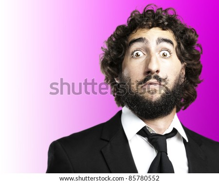 portrait of young man face afraid against a pink background - stock photo