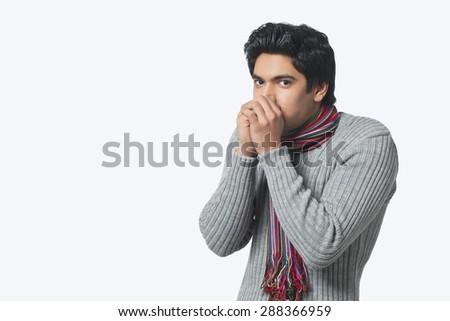 Portrait of young man feeling cold - stock photo