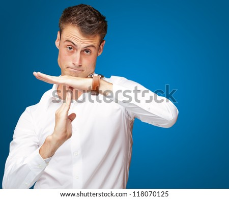 Portrait Of Young Man Gesturing Time Out Sign On Blue Background - stock photo
