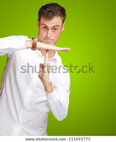 Portrait Of Young Man Gesturing Time Out Sign On Green Background