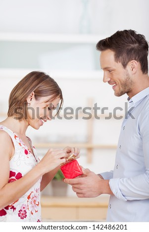 Portrait of young man gives his girlfriend a gift - stock photo