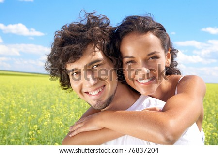 Portrait of young man giving beautiful woman piggyback in the field