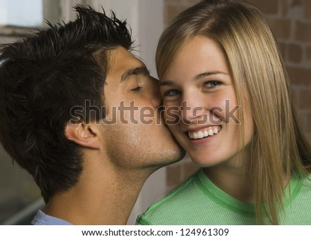 Portrait of young man giving kiss to his girlfriend - stock photo