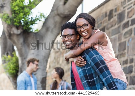 Portrait of young man giving piggyback to woman with friend background - stock photo