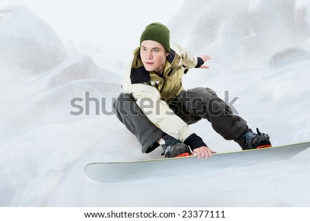 Portrait of young man going in for snowboarding in winter - stock photo