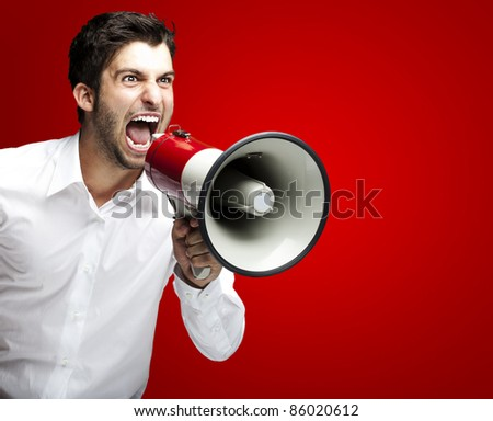 portrait of young man handsome shouting using megaphone over red background - stock photo