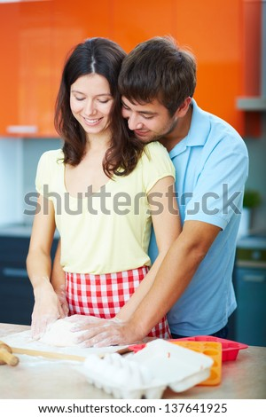 Portrait of young man his wife kneading dough in the kitchen - stock photo