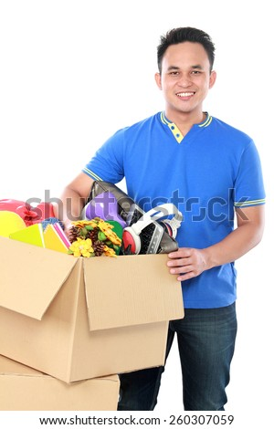 portrait of young man holding a box full of stuff on white background - stock photo