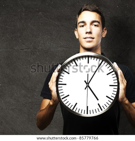 portrait of young man holding a clock against a grunge wall - stock photo