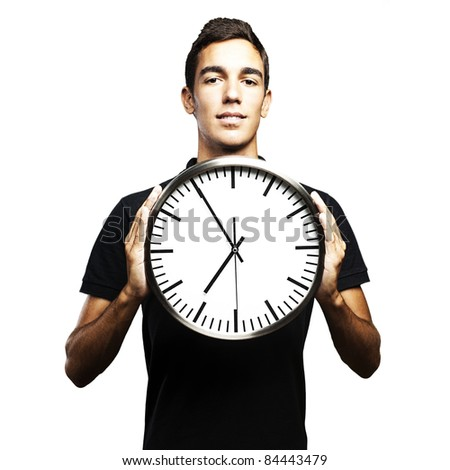 portrait of young man holding a clock with his hands over white background - stock photo