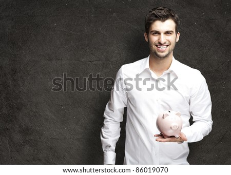 portrait of young man holding a piggy bank against a grunge background - stock photo