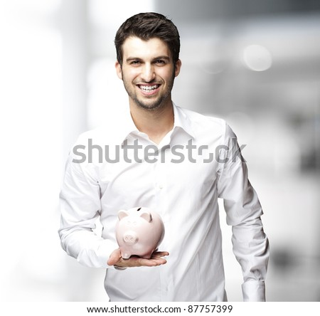 Portrait of young man holding a piggy bank indoor - stock photo