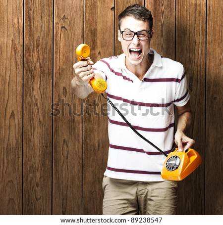 portrait of young man holding a vintage telephone against a wooden wall - stock photo
