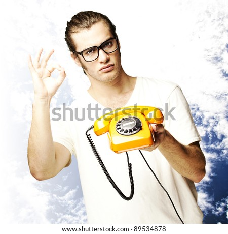 portrait of young man holding a vintage telephone and gesturing against a cloudy sky background - stock photo