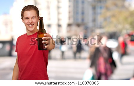 portrait of young man holding beer at crowded street