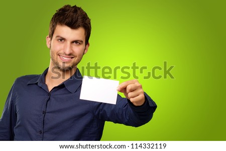 Portrait Of Young Man Holding Blank White Card against a green background