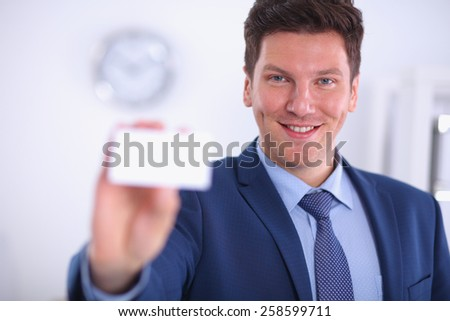 Portrait of young man holding blank white card, isolated - stock photo