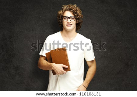 portrait of young man holding books against a grunge wall - stock photo