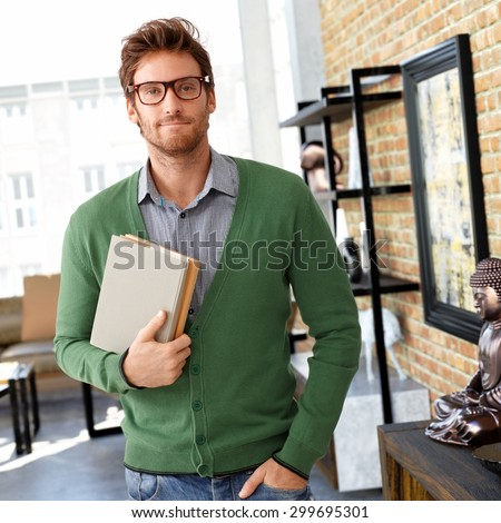 Portrait of young man holding books, looking at camera. - stock photo