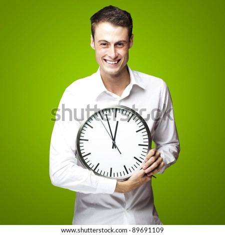 portrait of young man holding clock against a green background - stock photo