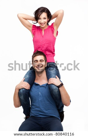 Portrait of young man holding his happy girlfriend on shoulders