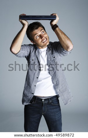 Portrait of young man holding laptop above his head, studio shot - stock photo
