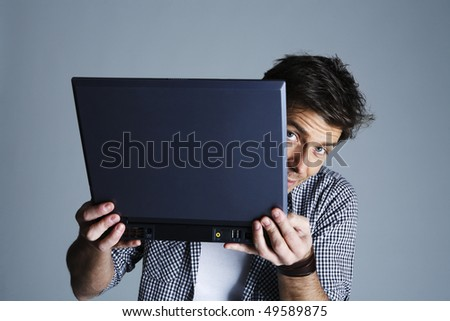 Portrait of young man holding laptop, studio shot - stock photo