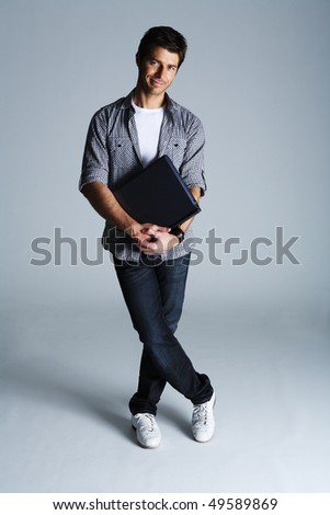 Portrait of young man holding laptop, studio shot on gray background - stock photo