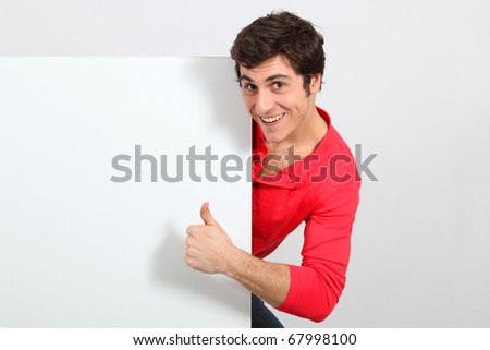 Portrait of young man holding whiteboard - stock photo