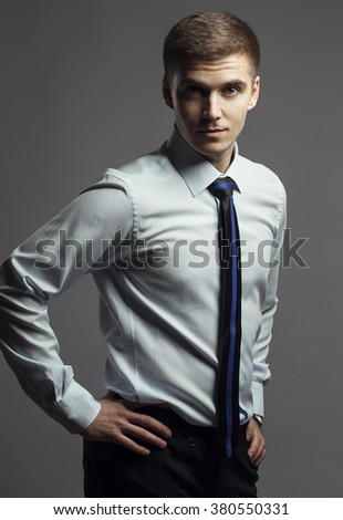 portrait of young man in a classic shirt and tie with blue line posing on a gray background. Concept of good  businessman