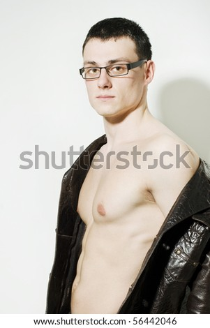 Portrait of young man in a leather jacket and glasses - stock photo