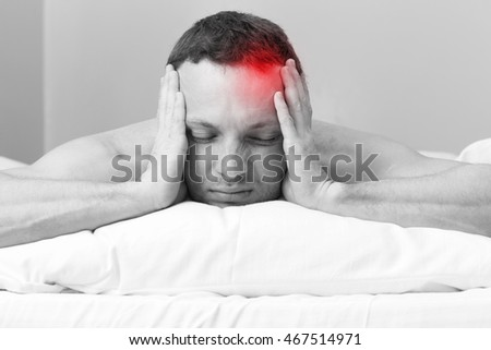 Portrait of Young man in bed with headache. Black and white stylized photo with red local ache spot