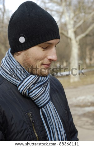 portrait of young man in black cap and striped scarf in the park. winter