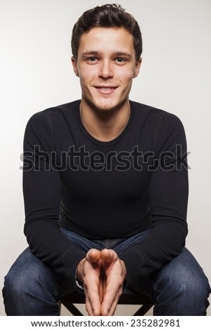 Portrait of young man in black shirt sitting on chair