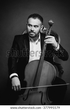 portrait of young man in black suit sitting on luxury chair with cello on dark background