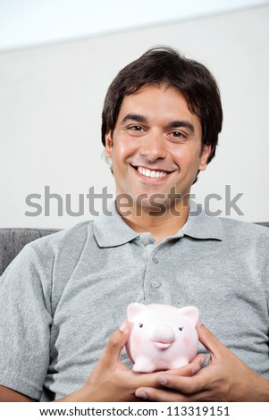 Portrait of young man in casual grey t-shirt smiling while holding piggybank