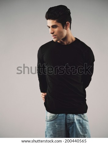 Portrait of young man in casuals looking away at copyspace. Hispanic male model on grey background - stock photo