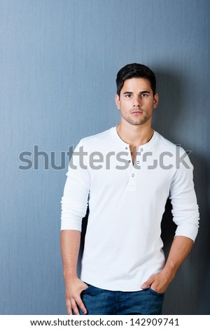 Portrait of young man in casuals with hands in pockets against blue wall