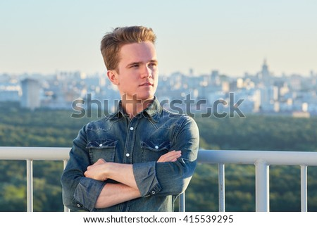 Portrait of young man in denim clothes stands crossing arms on chest on the roof leaning his back to the railing. - stock photo