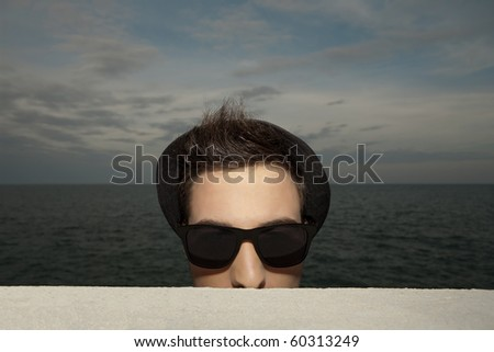Portrait of young man in hat and sunglasses standing near ledge at ocean at sunset - stock photo