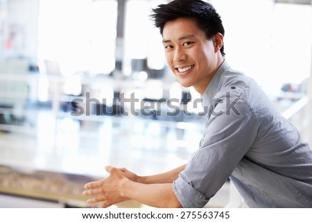Portrait of young man in office smiling - stock photo