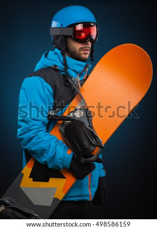 Portrait of young man in sportswear with snowboard. Studio shot