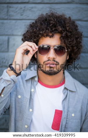 Portrait of young man in sunglasses leaning against wall - stock photo